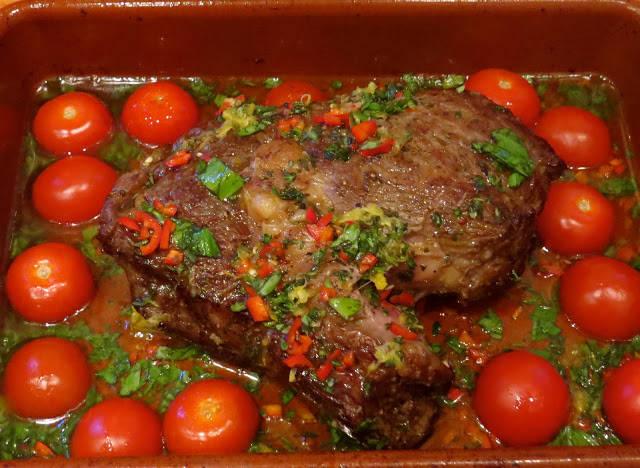 Ta ut formen fra ovnen: Når kjøttet er stekt ferdig (jeg liker det rødt i midten), lar du det ligge i den ildfaste formen og drysser over en god olivenolje (6-7 ss) og alle de deilige urtene. Snu kjøttet og sørg for at urtene og sitronskallet dekker flatene på kjøttet. Formen er nå varm fra ovnen og er du lur, legger du en drøss med halve cherrytomater i formen og lar de få suge opp de deilige saftene fra oljen og kjøttet. Legg med snittsiden ned. Damp noen grønne bønner og lag noen deilige frityrstekte (evt pannestekte) potetbåter.