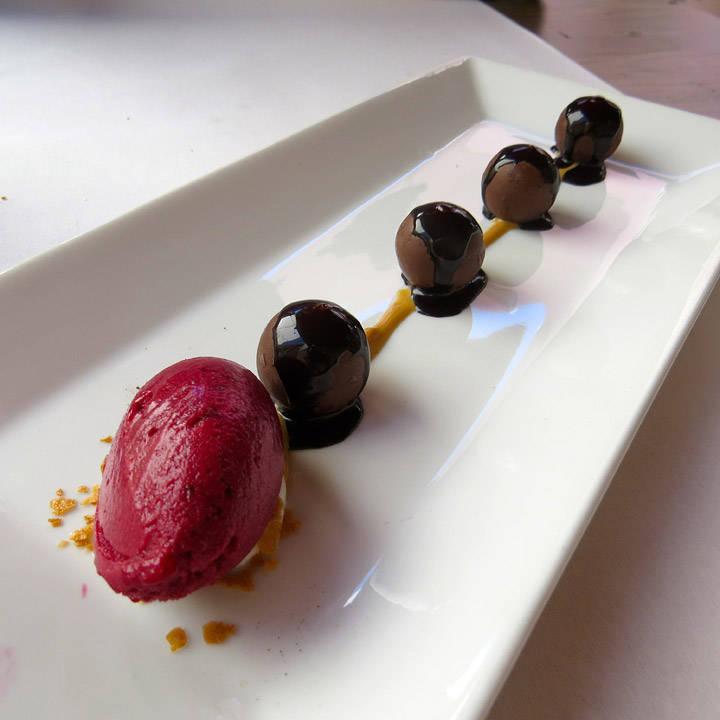 Sjokoladekuler med flytende sjokoladefyll servert med solbærsorbet og hasselnøttkrem. En eksplosjon i munnen.