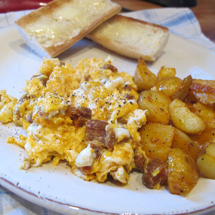 Rørte egg med chorizo, baguette og stekte poteter