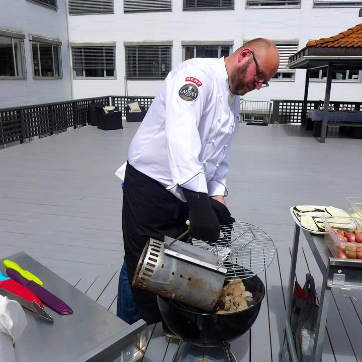 Espen heller grillbrikettene i grillen når de er grå. Han bruker et opptenningsrør for å få jevn varme på brikettene.