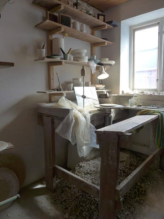 Arbeidsbenken og dreieskiven. All leiren som ligger på bakken, brukes på nytt.