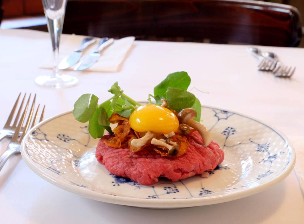 Rørt tartar servert med rå eggeplomme, syltede sopp og gulrotchips.