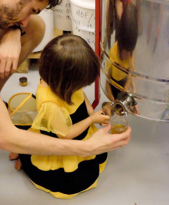 Denne jenta gikk helt opp i oppgaven. Her tappes honningen rett fra slyngen.